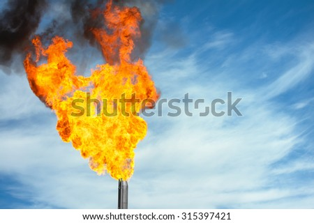Gas flaring. Torch against the sky. - stock photo