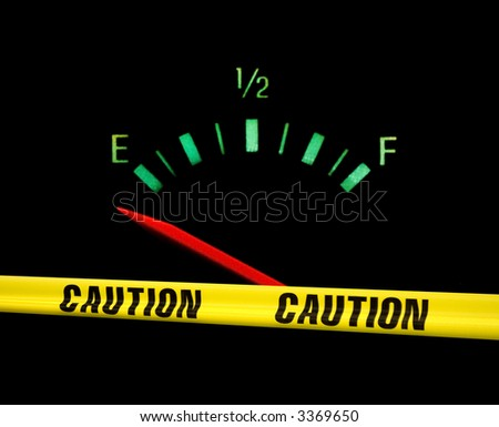 Gas gauge bright colors on empty on a black background with yellow caution tape across the front of it - stock photo