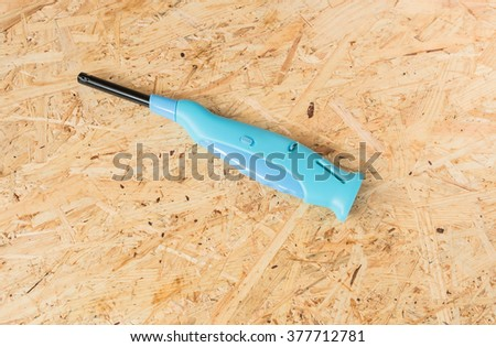 Gas lighter gun for gas-stove and gas-kitchen on wooden background - stock photo