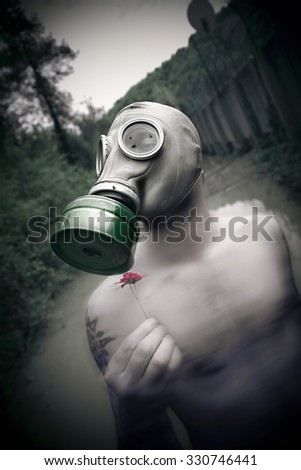 gas mask man smell flowers - stock photo