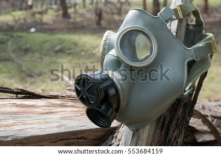 Gas mask on tree stump in deforested area with cutted tree