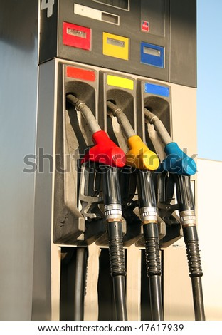 Gas nozzles at the gas station A row of 3 different gas pumps red yellow and blue - stock photo