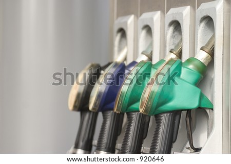 Gas nozzles at the gas station. Shallow depth of field with focus on the first nozzle. - stock photo