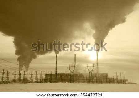 Gas power plant in cold winter landscape during sunset. Pipes with smoke. Power transmission tower foreground. Energy industry concept. Toned.