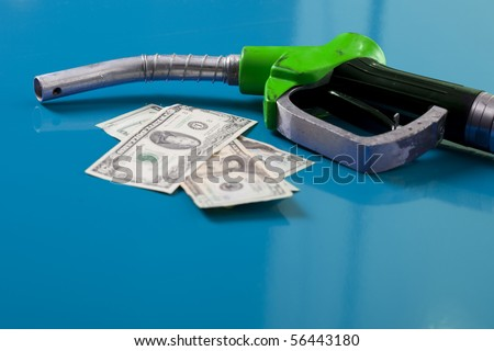 Gas price concept. American dollars and fuel nozzle