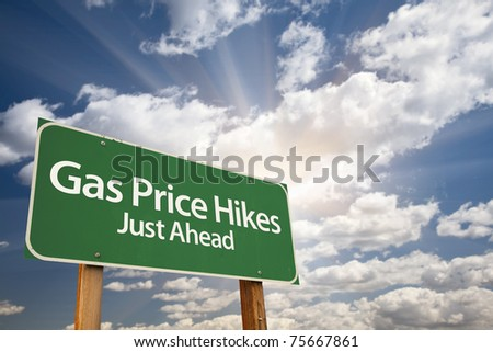 Gas Price Hikes Green Road Sign with Dramatic Clouds, Sun Rays and Sky. - stock photo