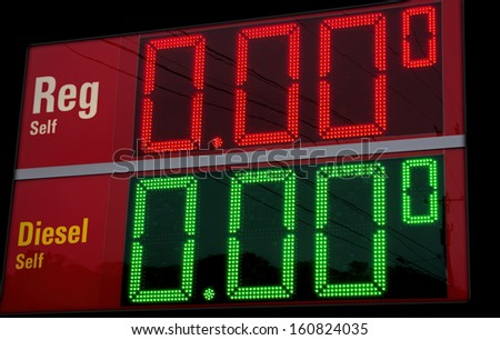 Gas prices crash!  Sign at an out of business gas station makes motorists smile and wish for the impossible. - stock photo