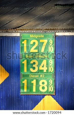 """Gas Prices:  Gasoline Price Sign from the """"Good Old Days."""" Sign on a rusty, old, colorful building. - stock photo"""