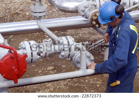 Gas production operator maintains well site - stock photo