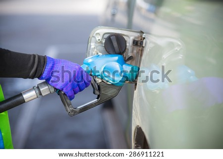 Gas pump nozzle in the fuel tank of a bronze car. - stock photo