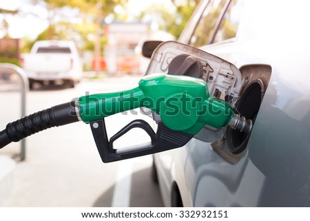 Gas pump nozzle in the fuel tank of a bronze car. refuel - stock photo