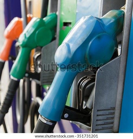 Gas pump nozzles in a service station - stock photo