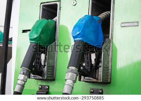 Gas pump nozzles in service station - stock photo