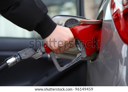 Gas pump refilling automobile fuel. Shallow focus. - stock photo