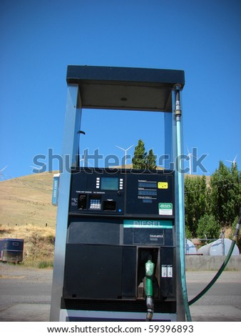 gas pump with wind turbines in background - stock photo