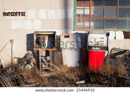 gas pumps - vintage gas pumps at an abandoned gas station in rural America with hot coffee sign - stock photo