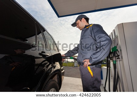 Gas station attendant filling up a car - stock photo