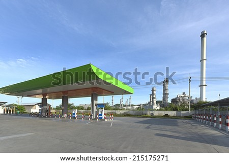 Gas Station near and refinery with blue sky - stock photo