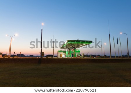 gas station under the night sky is shined with artificial lamps - stock photo