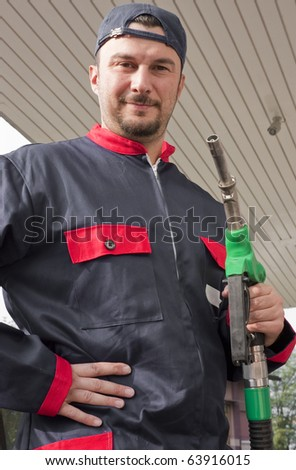 Gas Station Worker Refilling Car at Service Station - stock photo