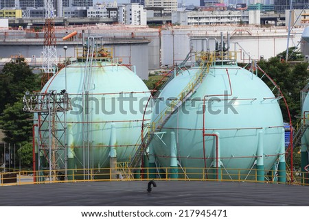 gas storage tank in oil refinery industry site with urban scene background - stock photo