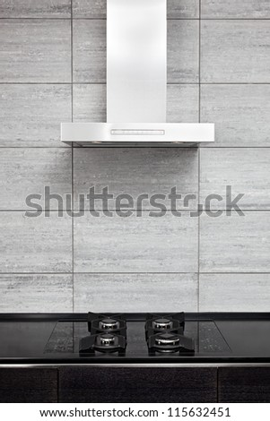 Gas-stove and cooking hood on modern minimalism style kitchen - stock photo