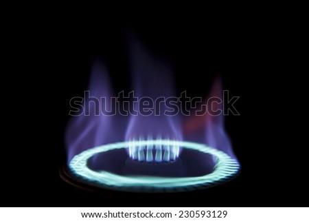 Gas stove burner in the dark - stock photo
