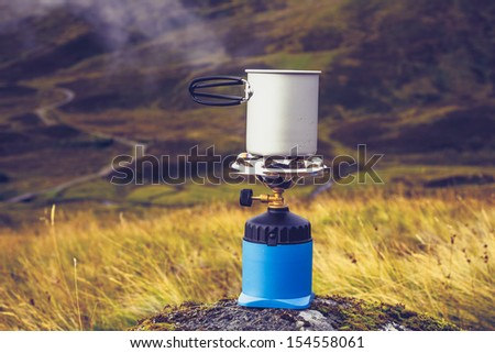 Gas stove with pot of boiling water in the mountains - stock photo