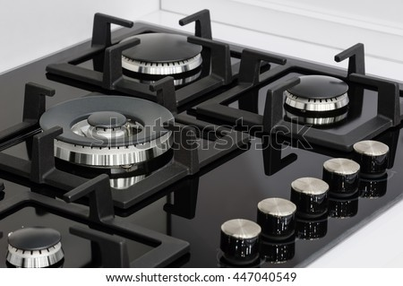 Gas stove with stainless tray selling in appliance retail store, closeup
