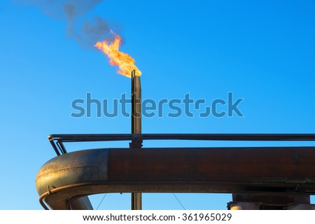Gas torch. Burning of associated gas at oil production. - stock photo