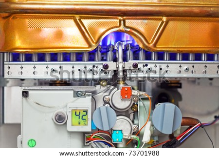 Gas water heater with the casing removed for survey and burning flame - stock photo