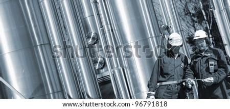 gas worker and gas pipelines, inside refinery, blue toning concept - stock photo