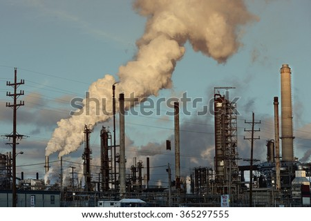 Gases coming out of smoke stacks at oil refinery - stock photo