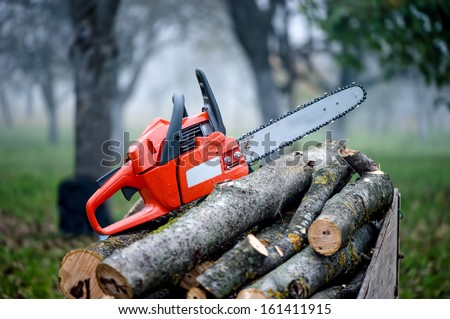 gasoline powered professional chainsaw on pile of cut wood - stock photo