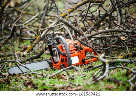 Gasoline professional chainsaw cutting branches against wood background  - stock photo