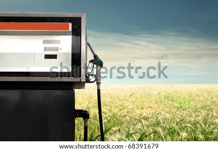 Gasoline pump with green meadow on the background - stock photo