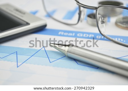 Gasses pen and calculator on financial chart and graph, accounting background - stock photo