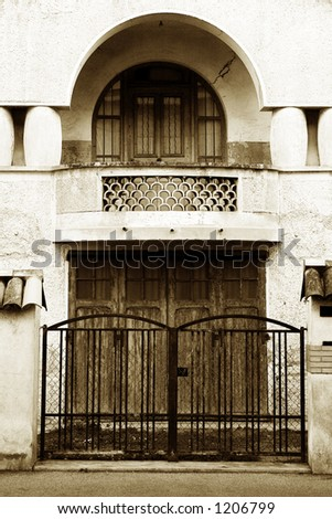 Gate and door of a building in Antibes, France.  Sepia tone. - stock photo