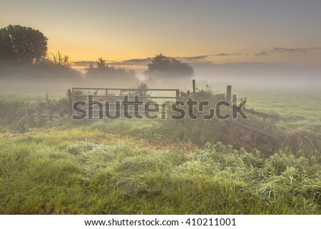 Gate and fences in Foggy farmland during sunrise in september, Drenthe Netherlands - stock photo