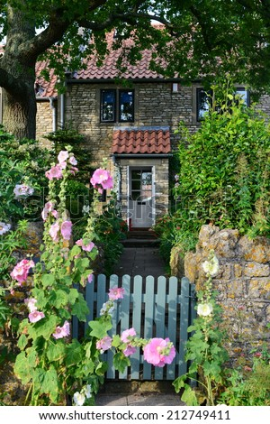 Gate and Pathway Leading to a Beautiful English Stone Cottage - stock photo