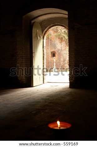 Gate leading to the outside, candle in the front - stock photo