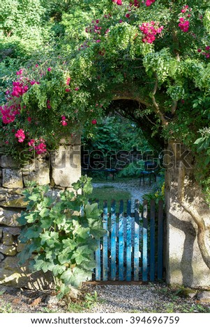 Gate of garden overgrown with roses in France