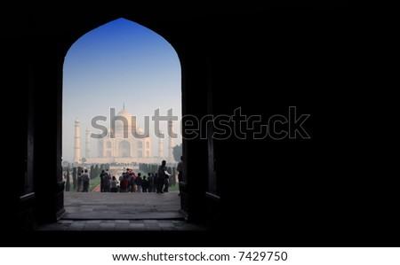 gate to worldwonder taj mahal in soft early morning light with blue sky - stock photo