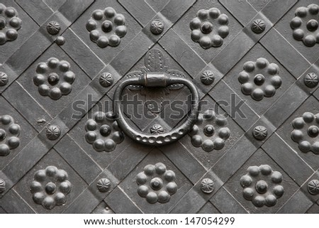 gate with door knocker, decorated with wrought iron - stock photo