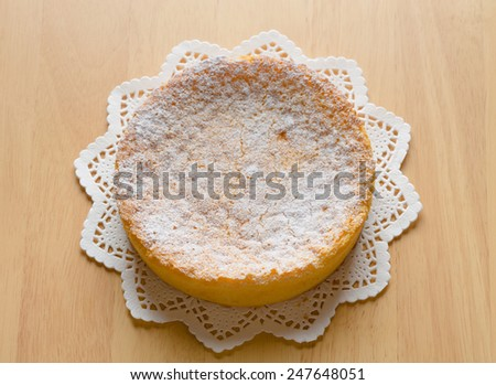 Gateau au chocolat blanc is a French cake made of white chocolate, butter, eggs, sugar, heavy cream, cognac liqueur, and vanilla pods' seeds; frosted with powdered sugar, served on a paper doily - stock photo
