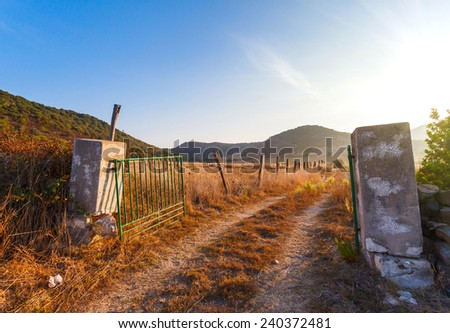 gates on the field a farm, yellow grass at the farmer's field in the rays of sunrise, Italy - stock photo