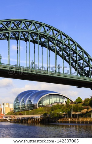 GATESHEAD, ENGLAND - MAY 16:  The Tyne Bridge connecting Newcastle and Gateshead in North East England.  Behind is the iconic Sage centre for musical education and performance  on May 16, 2013 - stock photo