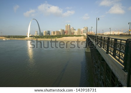 Gateway Arch and skyline of St. Louis, Missouri at sunrise from bridge in East St. Louis, Illinois on the Mississippi River - stock photo