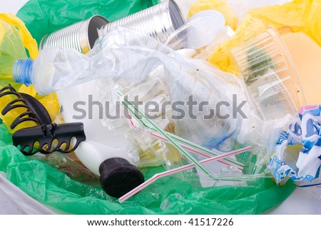 Gather garbage in green plastic bag dump lying on white, early spring season, Clean Up the World gathering. Earth Day and nature dispose, horizontal orientation, nobody.