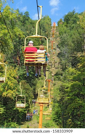 GATLINBURG, TENNESSEE - OCTOBER 6: Tourists ride the Sky Lift in Gatlinburg, Tennessee, October 6, 2013. Gatlinburg is a major tourist destination and gateway to Great Smoky Mountains National Park. - stock photo